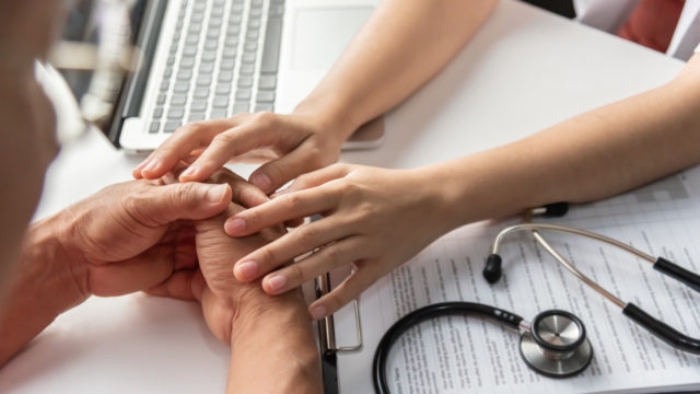 Female doctor holding hands of senior male patient.